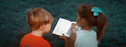 Duas crianças de costas sentadas na relva; uma delas mostra livro aberto à outra